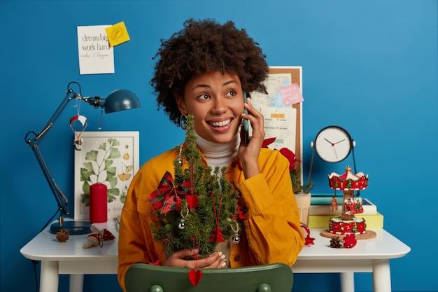 Senhora feliz aproveita o inverno, segura uma pequena árvore de natal decorada de verde, liga para um amigo via smartphone