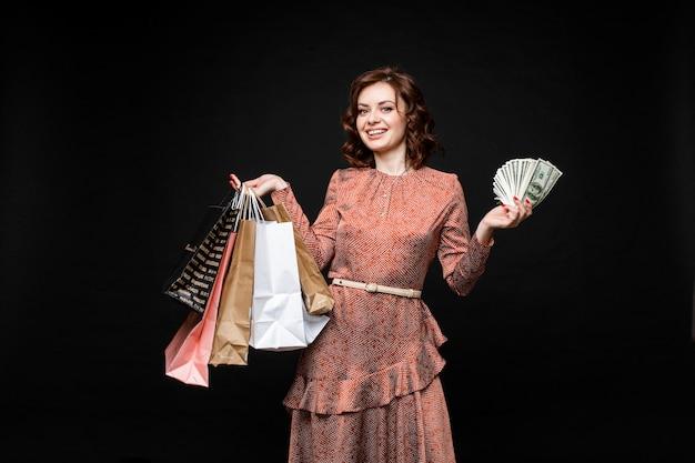 Senhora feliz com sacolas de compras e dinheiro nas mãos.