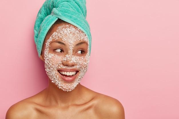 Senhora feliz com sorriso terno, refresca a pele com máscara de sal marinho, usa uma toalha enrolada na cabeça, tem ombros nus, desvia o olhar