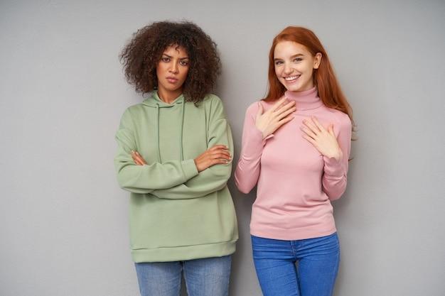 Senhora feliz de cabelos compridos com cabelo sexy, mantendo as palmas das mãos levantadas sobre o peito e sorrindo amplamente enquanto posava sobre uma parede cinza com uma mulher confusa de cabelos escuros encaracolados de pele escura