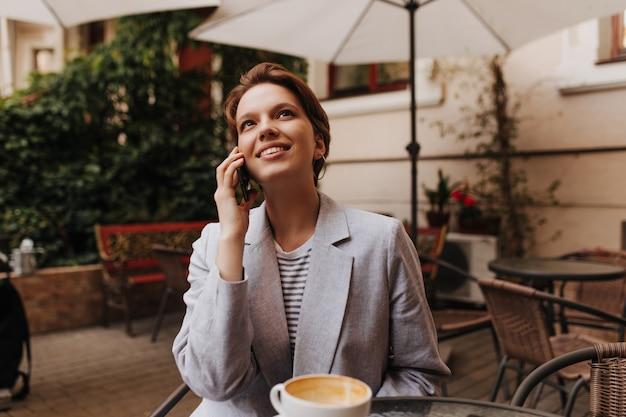 Senhora feliz descansando no café e falando no telefone. mulher charmosa de cabelo curto e jaqueta cinza sorrindo e relaxando lá fora