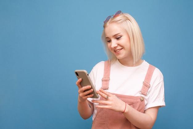 Senhora feliz em roupas brilhantes com um smartphone na mão é isolada em um fundo azul.