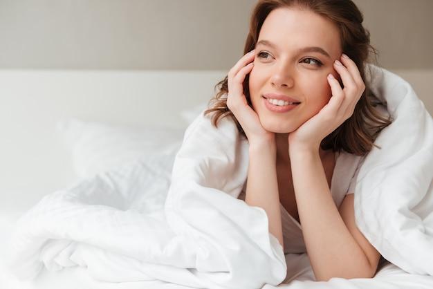 Senhora feliz encontra-se na cama dentro de casa