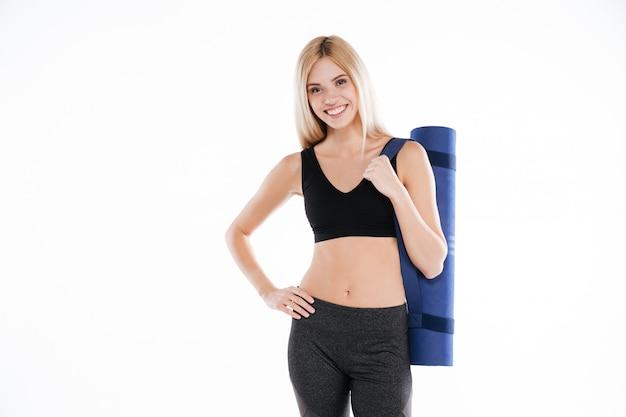 Senhora feliz fitness segurando o tapete de esportes