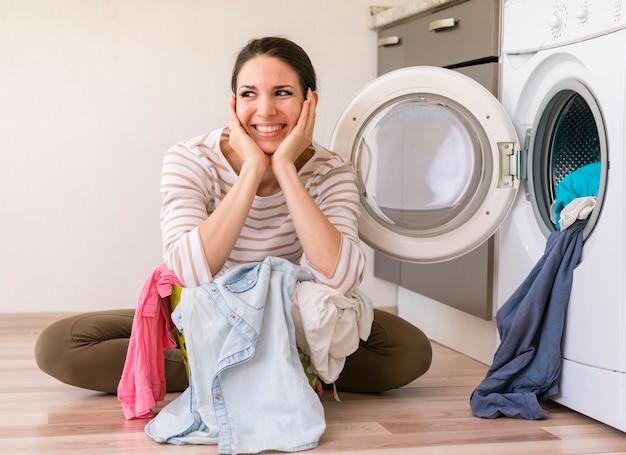 Senhora feliz lavando roupa vista frontal