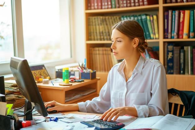 Senhora feliz nova do negócio na camisa branca que senta-se na tabela com computador e papéis que trabalham o ambiente.