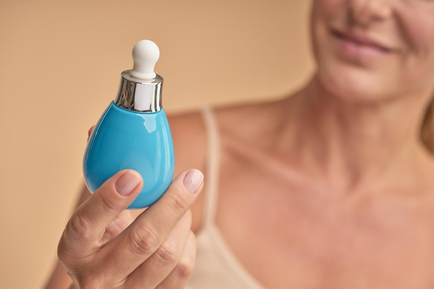 Senhora feliz segurando um produto profissional para cuidados do rosto