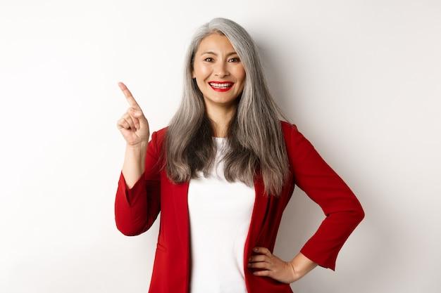 Senhora feliz sênior do escritório apontando o dedo no canto superior esquerdo, mostrando o logotipo da empresa e sorrindo para a câmera, em pé sobre um fundo branco. copie o espaço