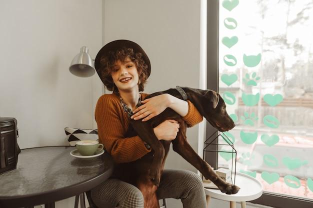 Senhora feliz tomando café e brincando com o cachorro na cafeteria