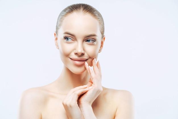 Senhora feminina olha de lado toca o rosto suavemente olha sensual e relaxada aplica maquiagem