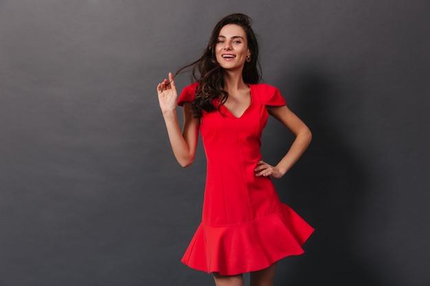 Senhora frágil com sorrisos com covinhas nas bochechas. senhora de vestido vermelho sorri e brinca com cabelos em fundo preto.