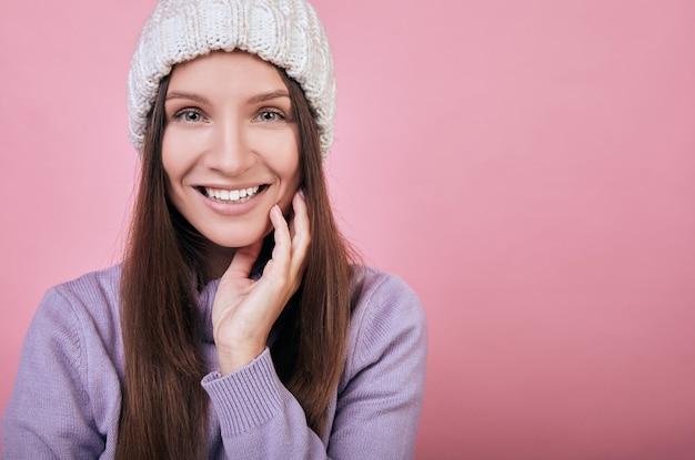 Senhora gentil está usando um chapéu de malha branca e um suéter delicadamente roxo