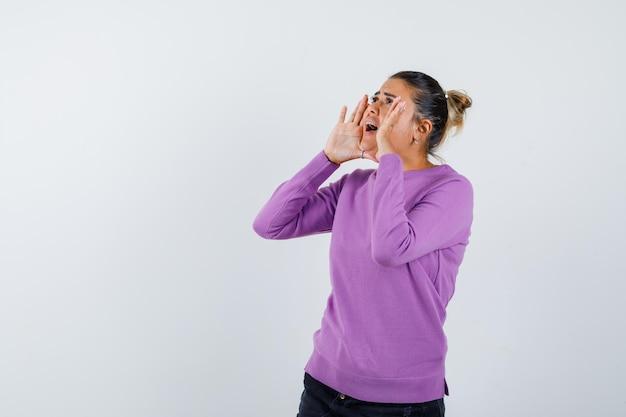 Senhora gritando ou anunciando algo em uma blusa de lã e parecendo animada