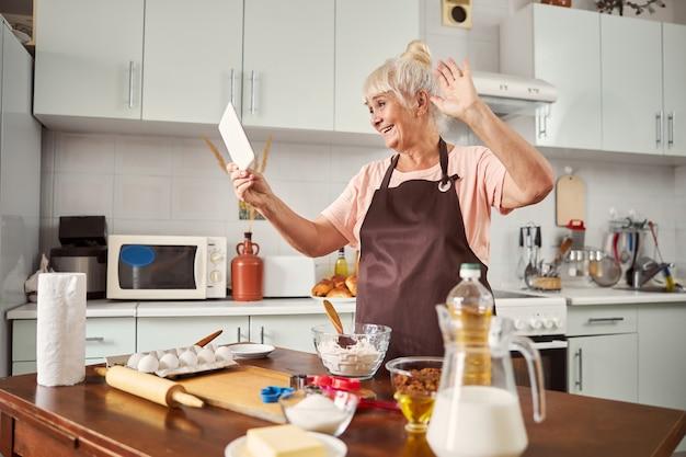 Senhora idosa alegre fazendo uma videochamada da cozinha