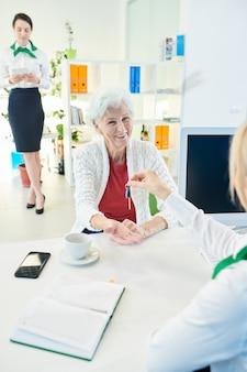 Senhora idosa animada feliz recebendo a chave do novo apartamento