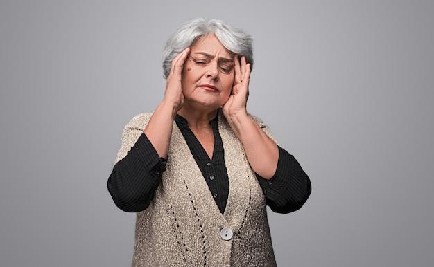 Senhora idosa com enxaqueca forte