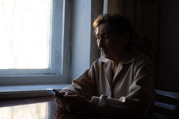 Senhora idosa com smartphone em casa
