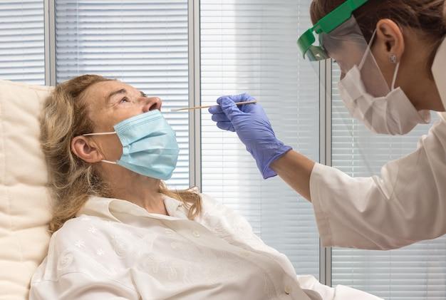 Senhora idosa com uma camisa branca e máscara sentada enquanto uma enfermeira com proteção anti-covid-19 faz o teste de pcr
