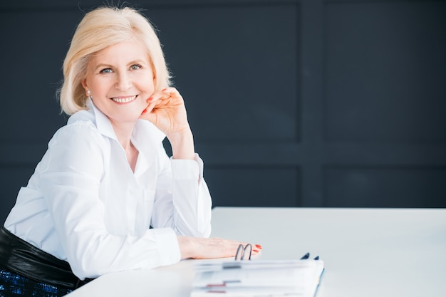 Senhora idosa de sucesso. poder feminino. mulher de negócios sorridente no local de trabalho