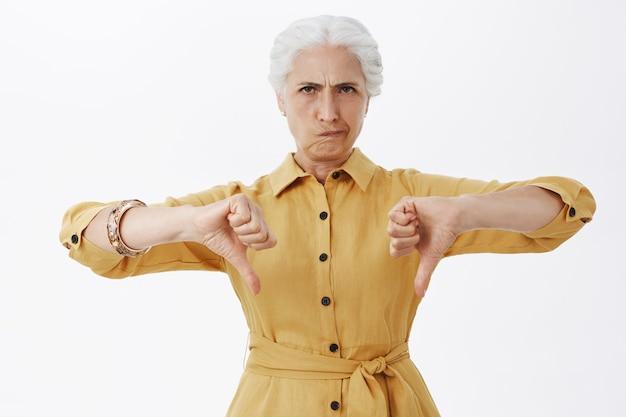 Senhora idosa decepcionada franzindo a testa e mostrando o polegar para baixo