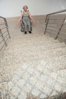 Senhora idosa em cadeira de rodas presa no fundo das escadas