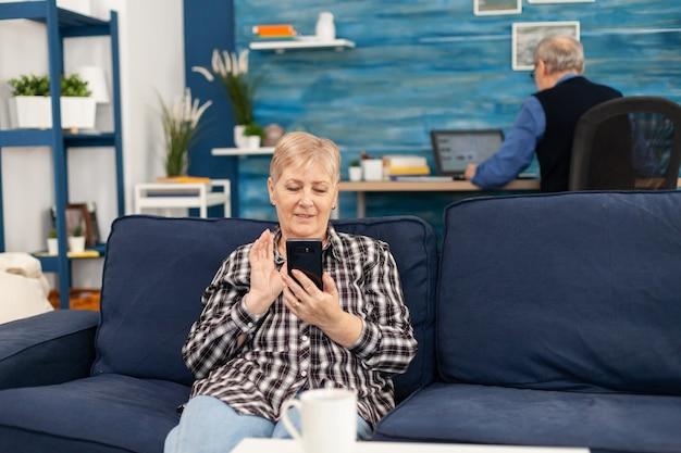 Senhora idosa feliz acenando para um smartphone durante a videochamada