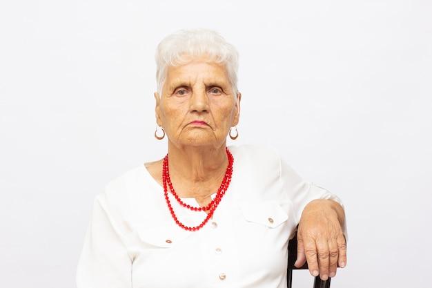 Senhora idosa muito atraente sorrindo isolada no branco