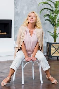 Senhora idosa na moda posando na cadeira