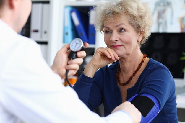 Senhora idosa sorridente na blusa azul com retrato do doutor