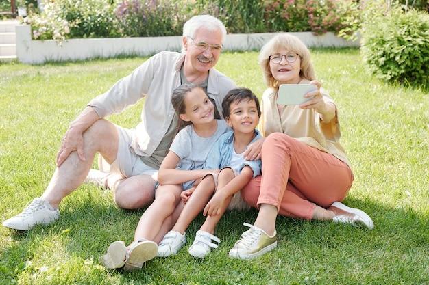 Senhora idosa tirando foto de si mesma, do marido e dos netos na câmera do smartphone
