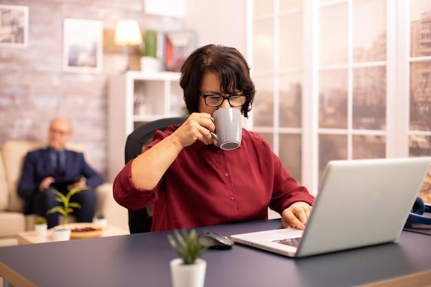 Senhora idosa tomando um gole de café enquanto trabalha em um laptop moderno em uma sala de estar aconchegante