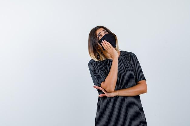 Senhora inclinando a bochecha na palma da mão em um vestido preto, máscara médica e olhando pensativa, vista frontal