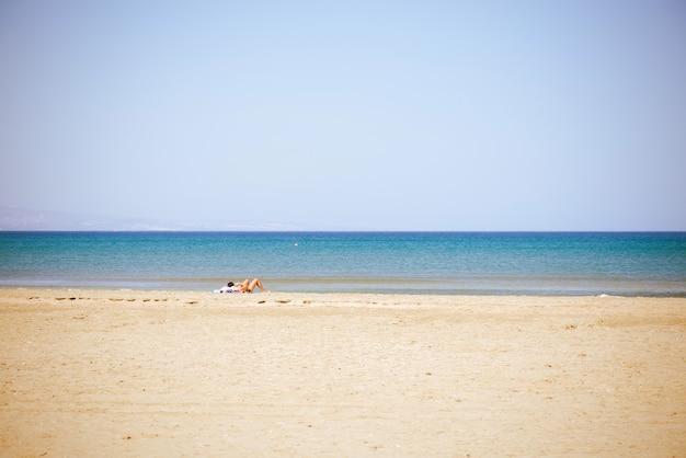 Senhora indefinida deitada na praia de verão