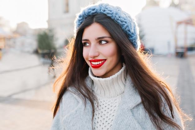 Senhora inspirada de cabelos escuros com maquiagem brilhante, olhando para longe durante um passeio pela cidade no inverno. foto de close-up de uma mulher morena deslumbrante com penteado reto, sonhando com algo na rua.