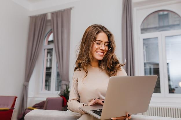 Senhora inteligente e alegre de óculos trabalhando com um laptop em um quarto aconchegante