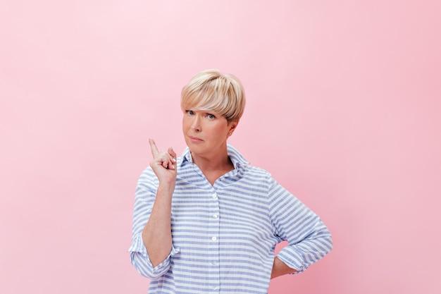 Senhora inteligente em roupa azul tem uma ideia e posa pensativamente sobre um fundo rosa