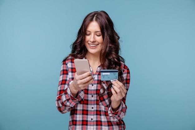 Senhora isolada sobre o fundo azul, usando o telefone móvel, segurando o cartão de crédito.