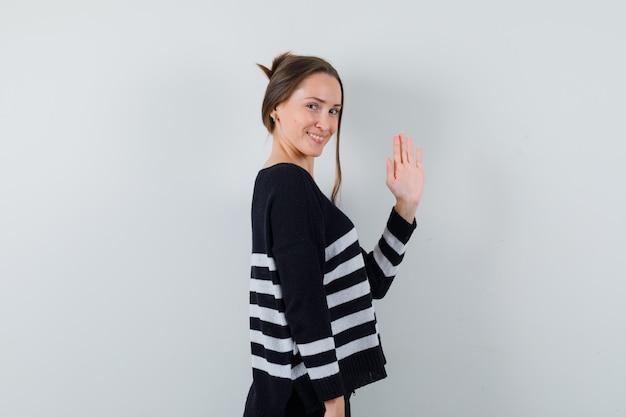 Senhora jovem acenando com a mão para se despedir de camisa e parecendo jovial