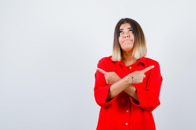 Senhora jovem apontando para os dois lados em uma camisa vermelha grande demais e parecendo indecisa, vista frontal.