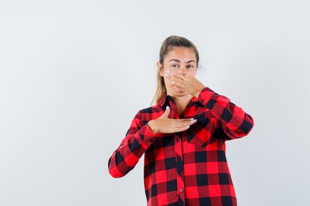 Senhora jovem beliscando o nariz devido ao mau cheiro em uma camisa quadriculada e parecendo enojada