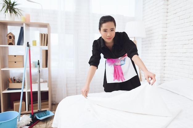 Senhora jovem dona de casa organiza cama no hotel.