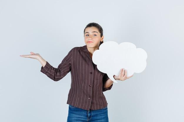 Senhora jovem espalhando a palma da mão, mantendo o pôster de papel na camisa, jeans e parecendo perplexo, vista frontal.
