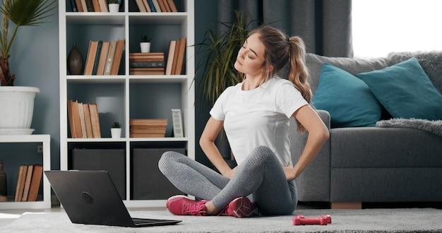 Senhora jovem sentada com as pernas dobradas e cabeça inclinada no chão aquecendo antes do treino