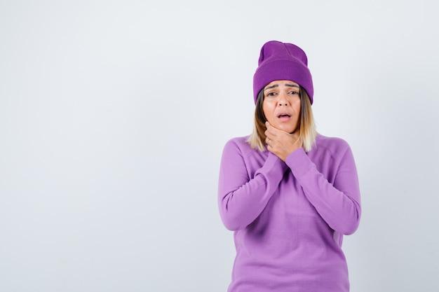 Senhora jovem sofrendo de dor de garganta no suéter roxo, gorro e parecendo dolorido. vista frontal.