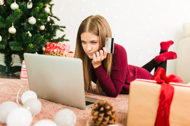 Senhora jovem, usando computador portátil, com, cartão crédito, perto, presente boxeia, e, natal, árvore abeto