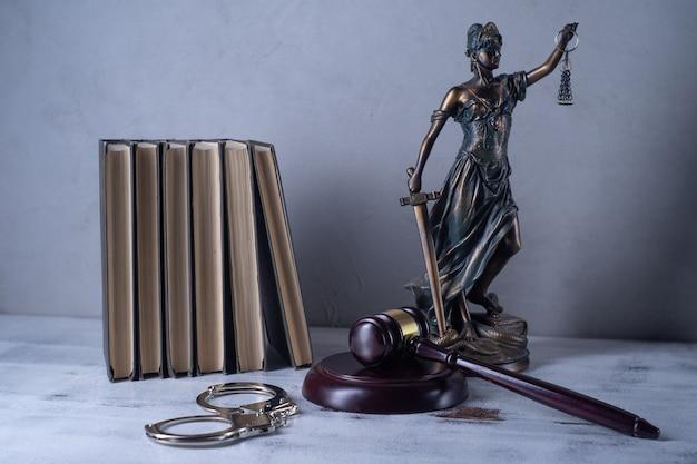 Senhora justiça, martelo do juiz, livros, algemas em uma velha mesa de madeira