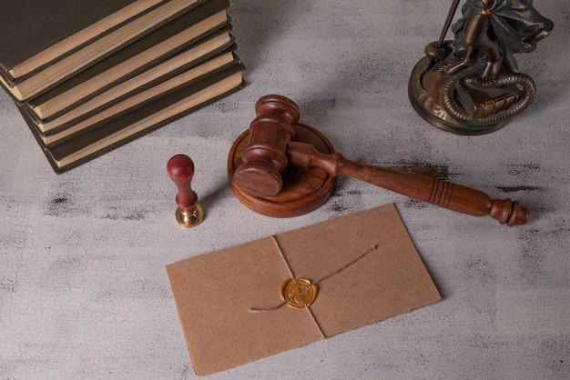 Senhora justiça, martelo do juiz, livros, rolo de pergaminho com selo e carimbo em uma velha mesa de madeira