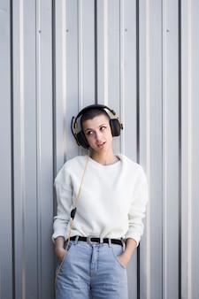 Senhora legal com a cabeça raspada, ouvindo música