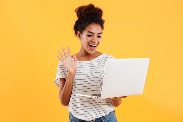 Senhora legal positiva jovem com cabelos cacheados usando laptop isolado