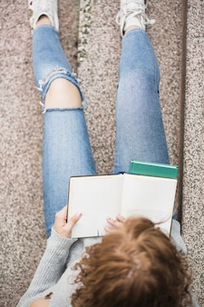 Senhora lendo livro sobre as etapas